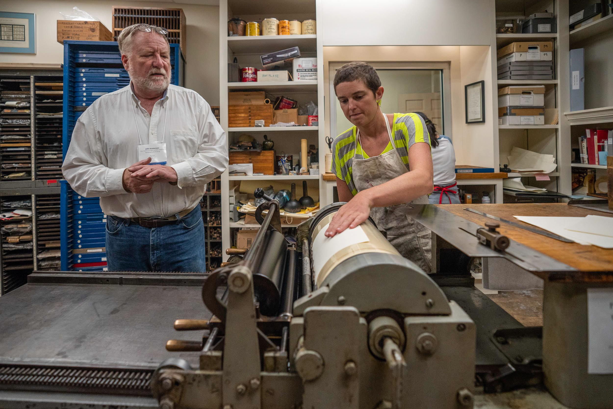 Instructor John Kristensen watches as student Meghan Forbes works the Vandercook proof press.