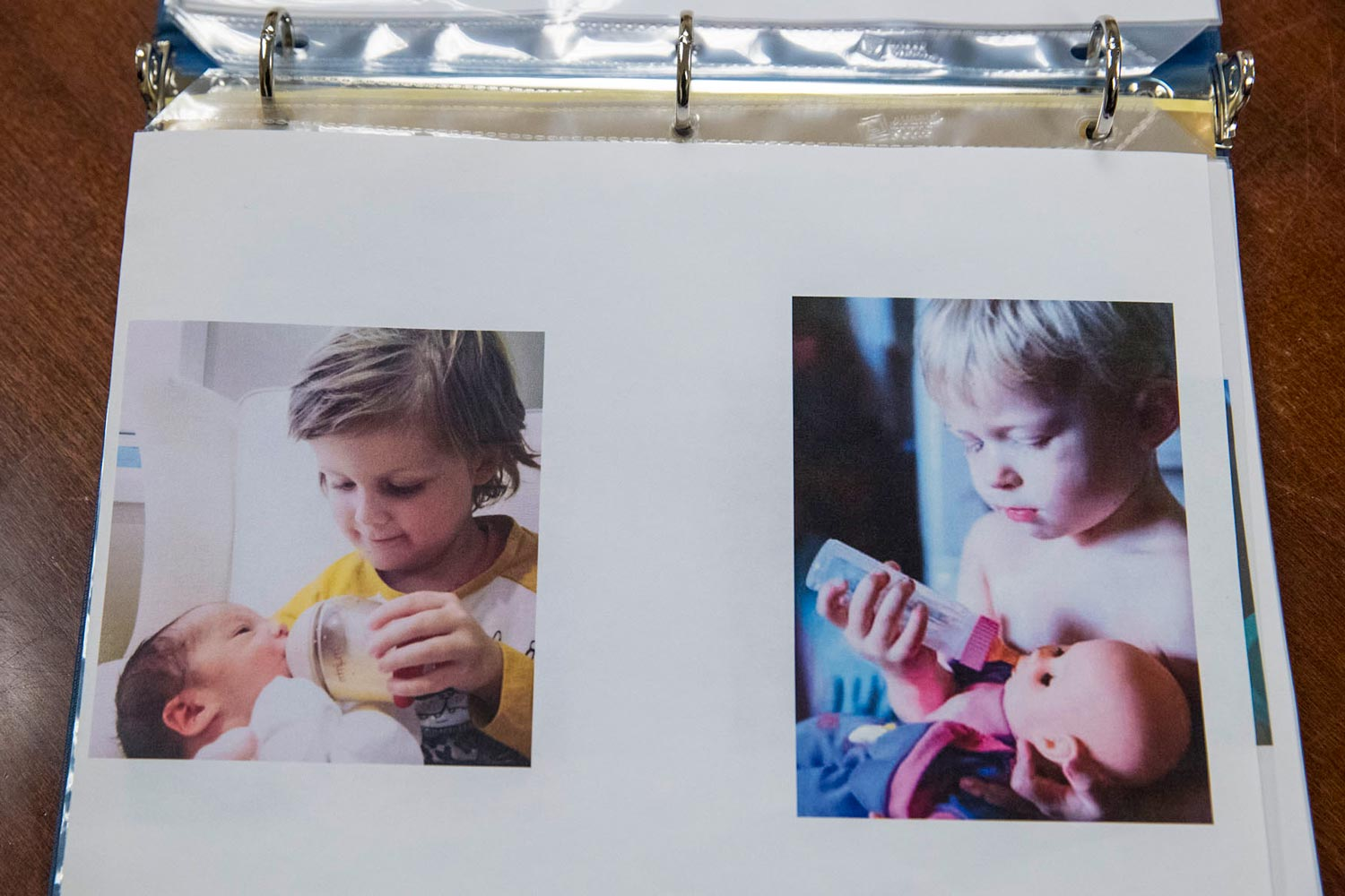Two photos in a binder: a small child bottle-feeding a baby, and a small child bottle-feeding a doll