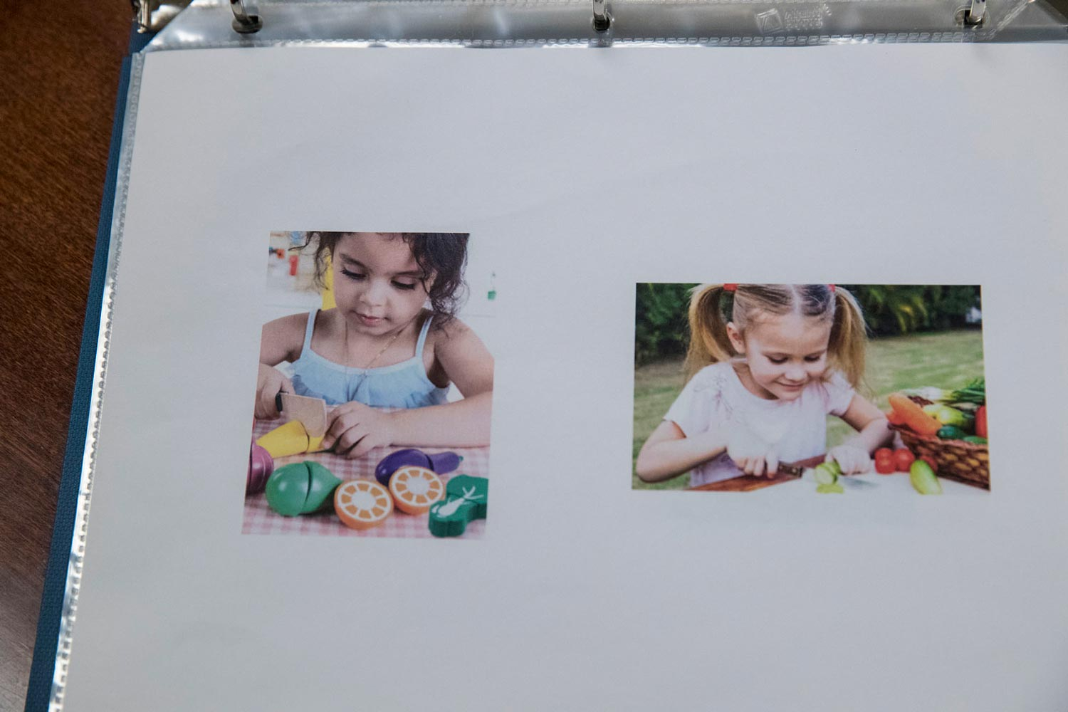 Two photos in a binder: a small child cutting a toy vegetable with a toy knife, and a small child cutting a real vegetable with a real knife.