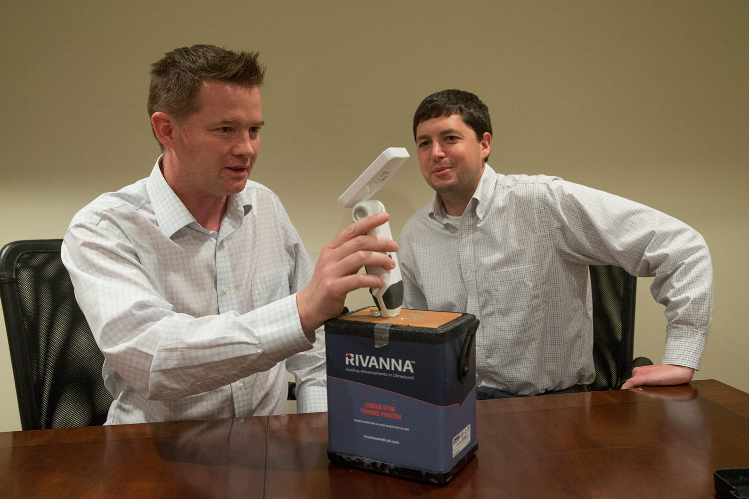 Kevin Owen (left) demonstrates the Accuro device's spine-finding capabilities through layers of synthetic skin while his co-founder Will Mauldin looks on.