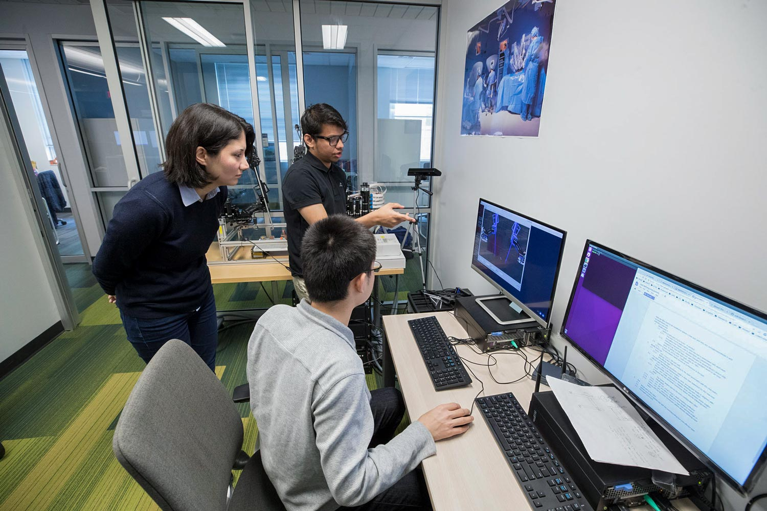 Alemzadeh works with students Samin Yaser, rear, and Yonming Qin. The team hopes to provide more realistic training simulations of robotic surgery.