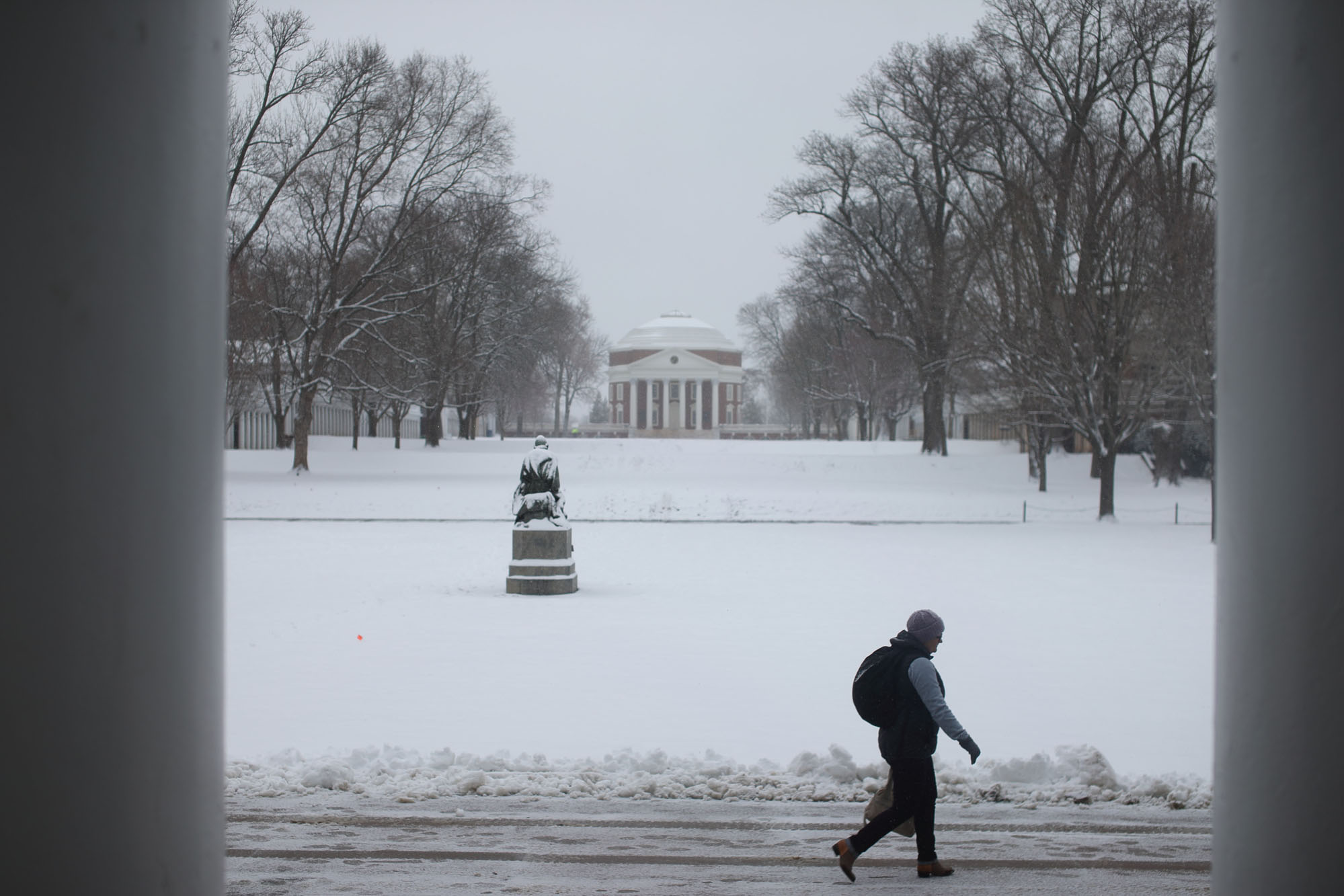 Student walking on a snowy lawn