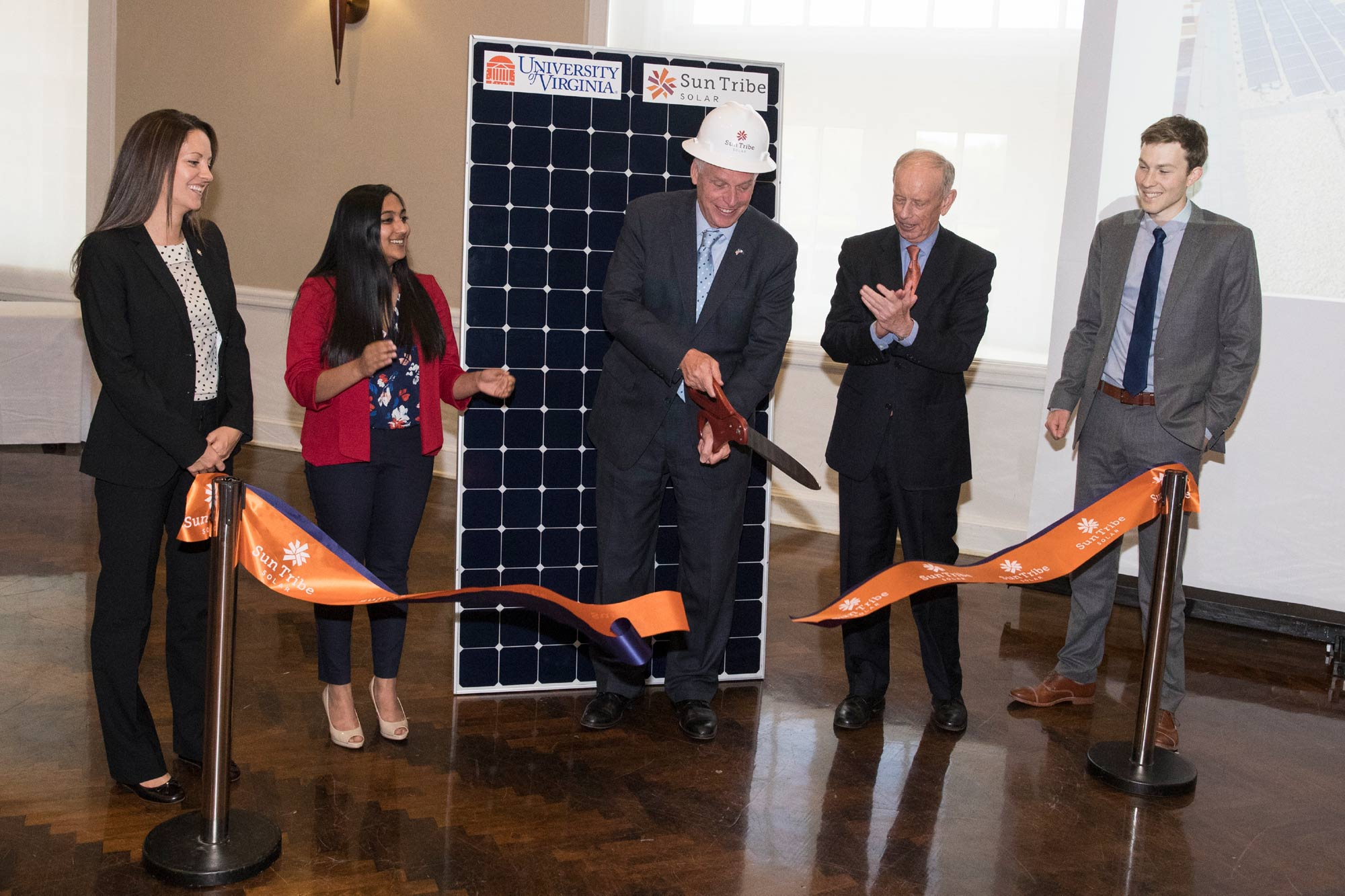 Virginia Gov. Terry McAuliffe cuts a ceremonial ribbon launching a solar array on Clemons Library that will provide 15 percent of the building's electricity.