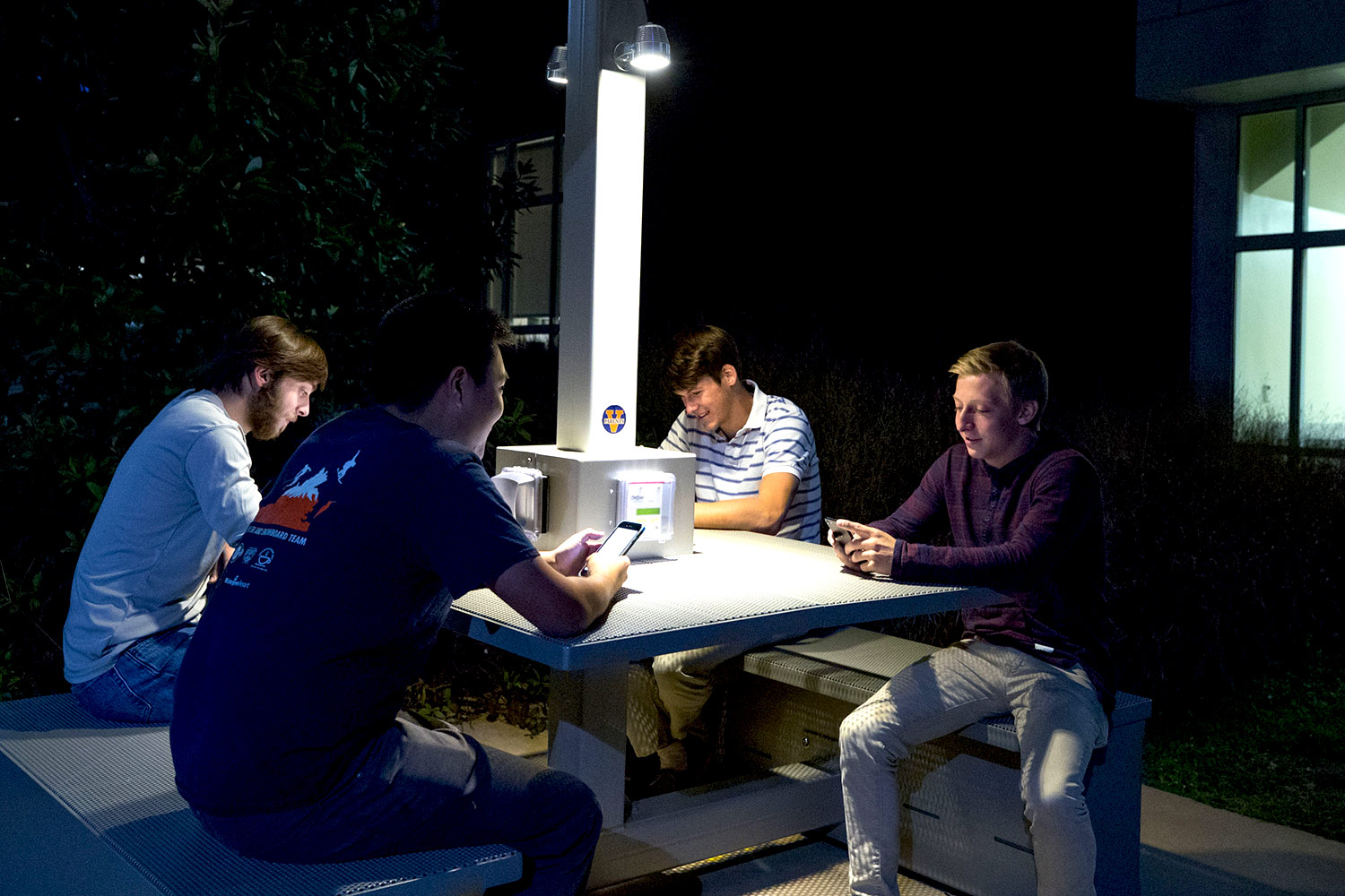 From left, students Kevin Meyers, Christopher Kim, Matt Denecke and Nicholas Anselmo use their mobile telephones at Lile-Maupin House's solar table. (Photo by Sanjay Suchak, University Communications)