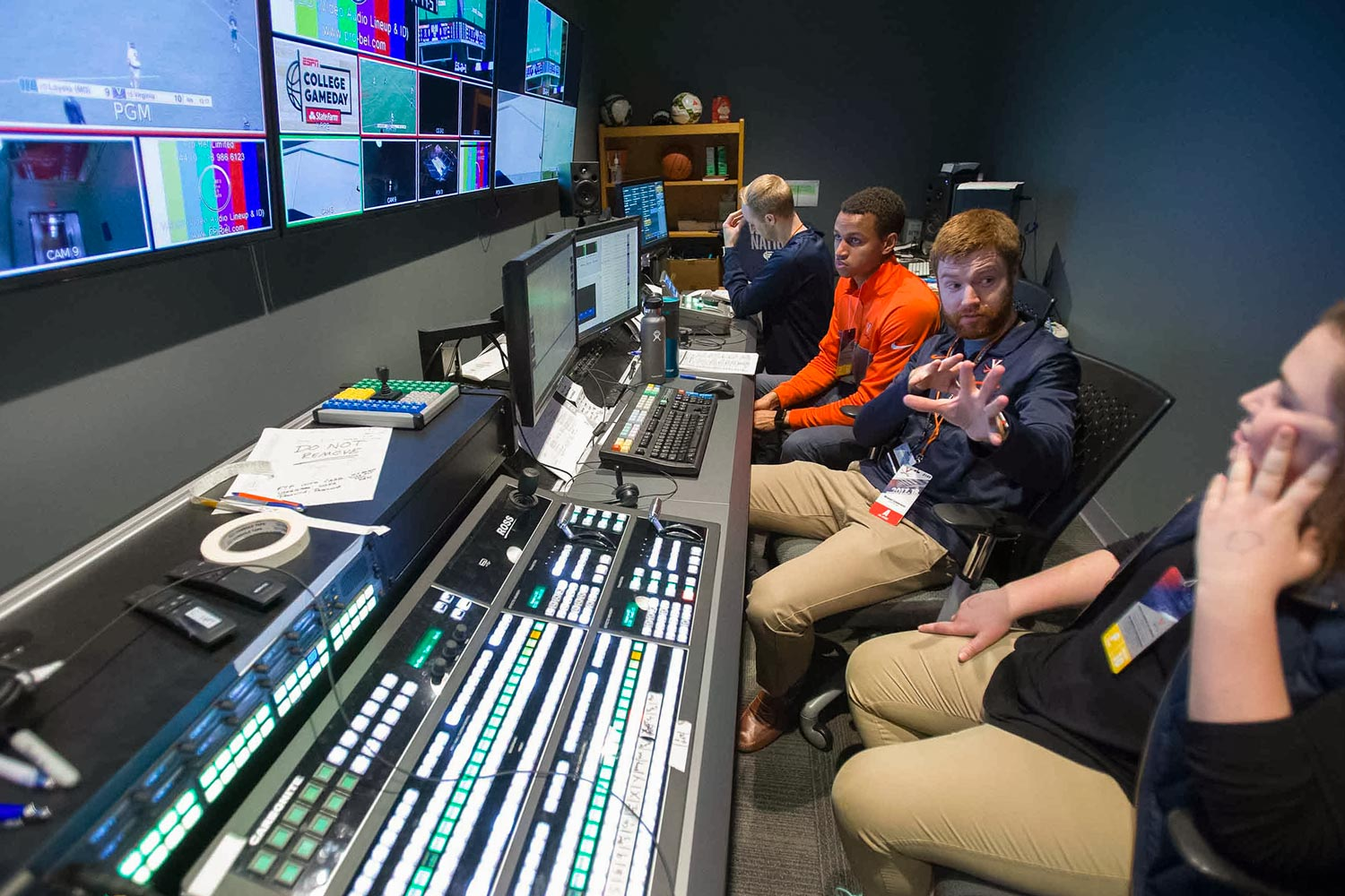 UVA Video Services senior producer Michael Szlamowicz, center, helps media production students learn about the John Paul Jones Arena production studio.