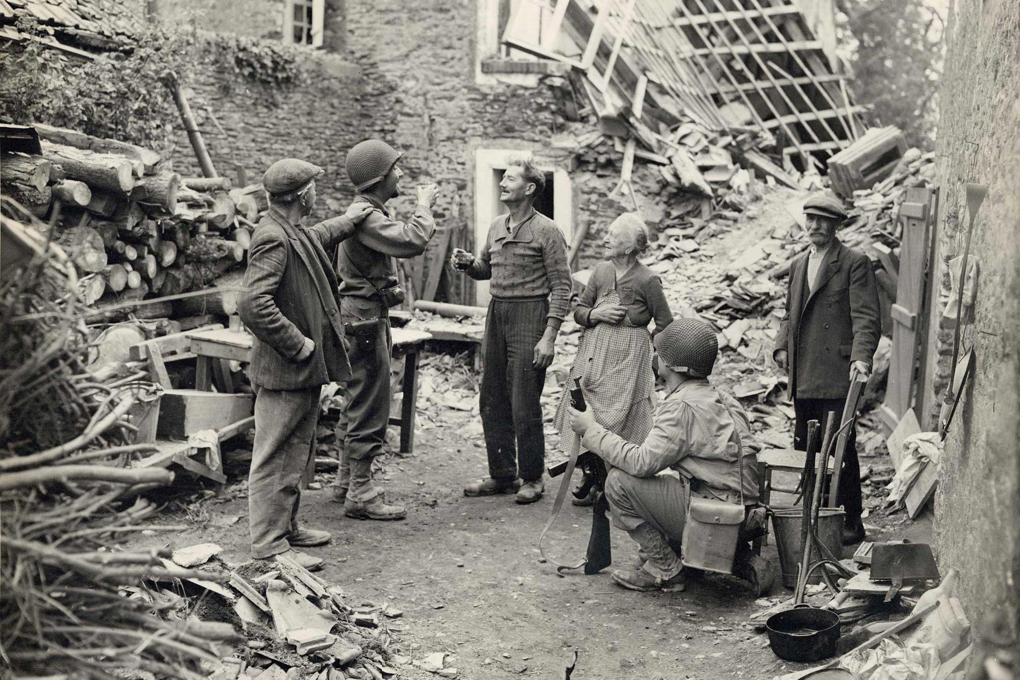 An American Army officer and a French civilian share a toast amidst the rubble of the town of Saint-Lô.