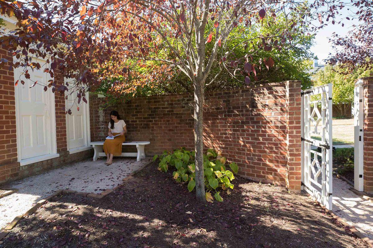 Student Alexandra Pentel reads in a quiet corner of Pavilion IX's garden.