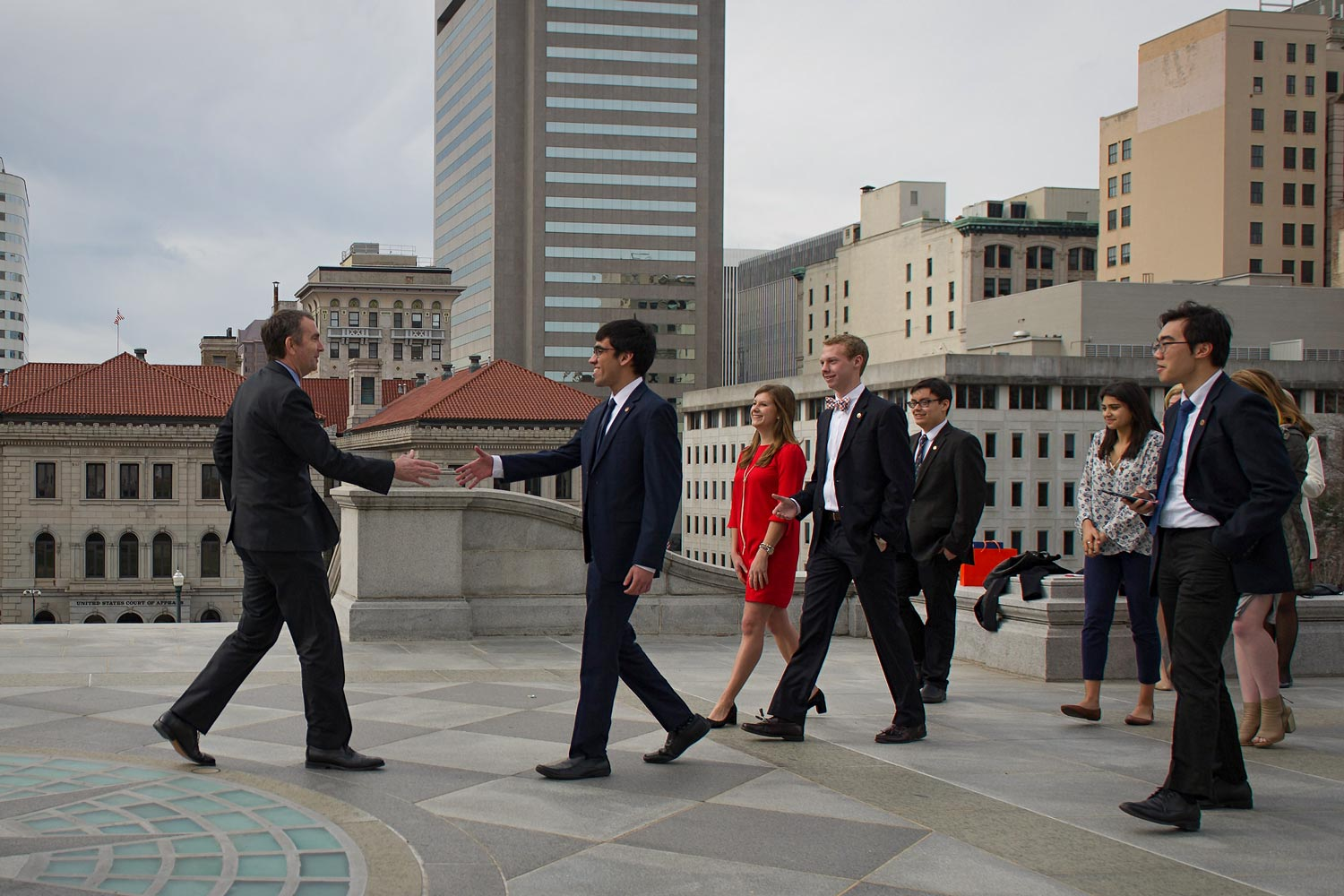 Young people walk toward a man in a suit, preparing for a handshake