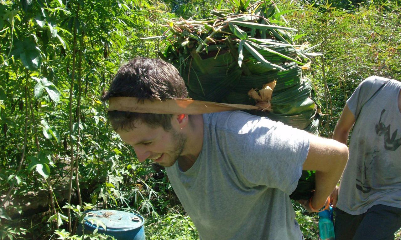 bd93a394b71 U.Va. student Elliott Oakley carries a bag of sweet potatoes on his back