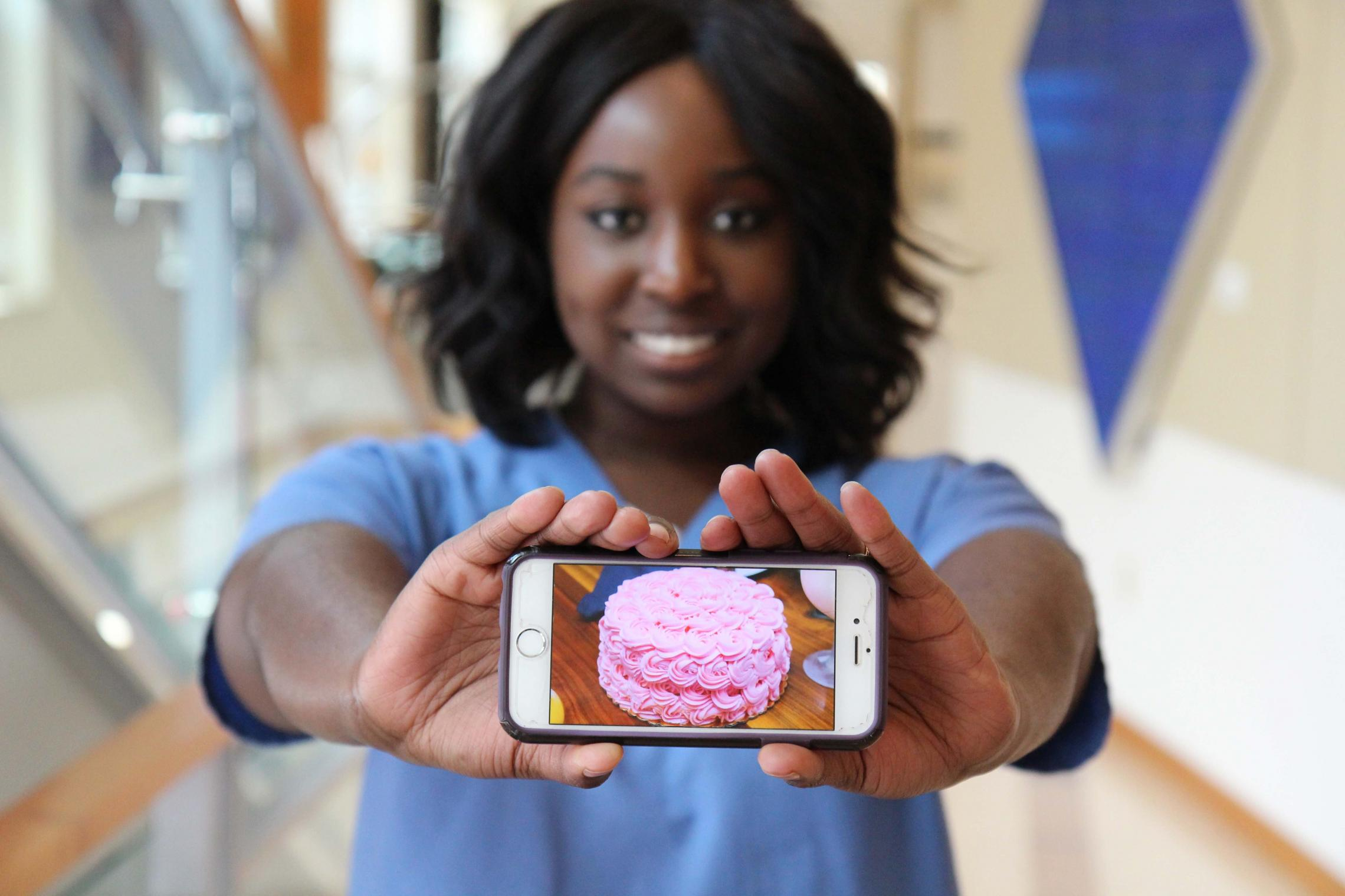 Michelle Bonsu displays one of her confectionary creations. She earned degrees psychology and anthropology from the College of Arts and Sciences in 2015.