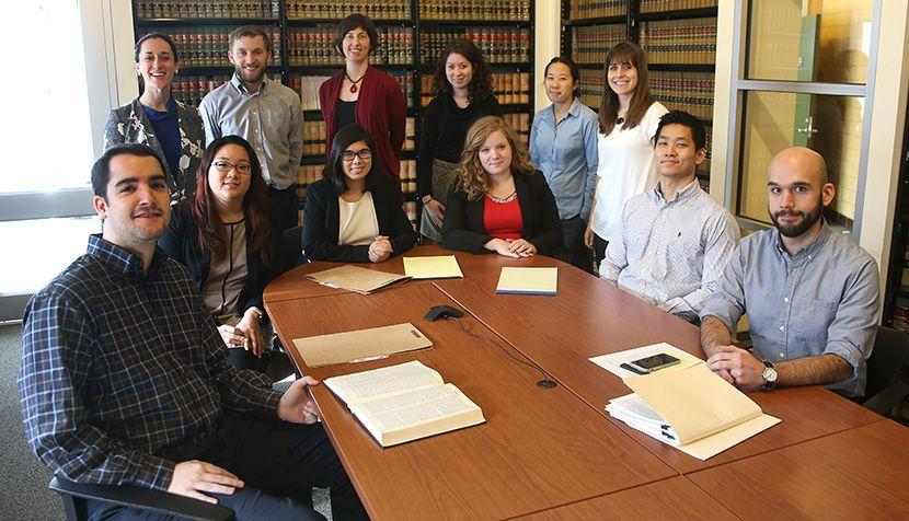 UVA Law students who volunteered during winter break gather around a table at the Legal Aid Justice Center with staff also assigned to the caseload.