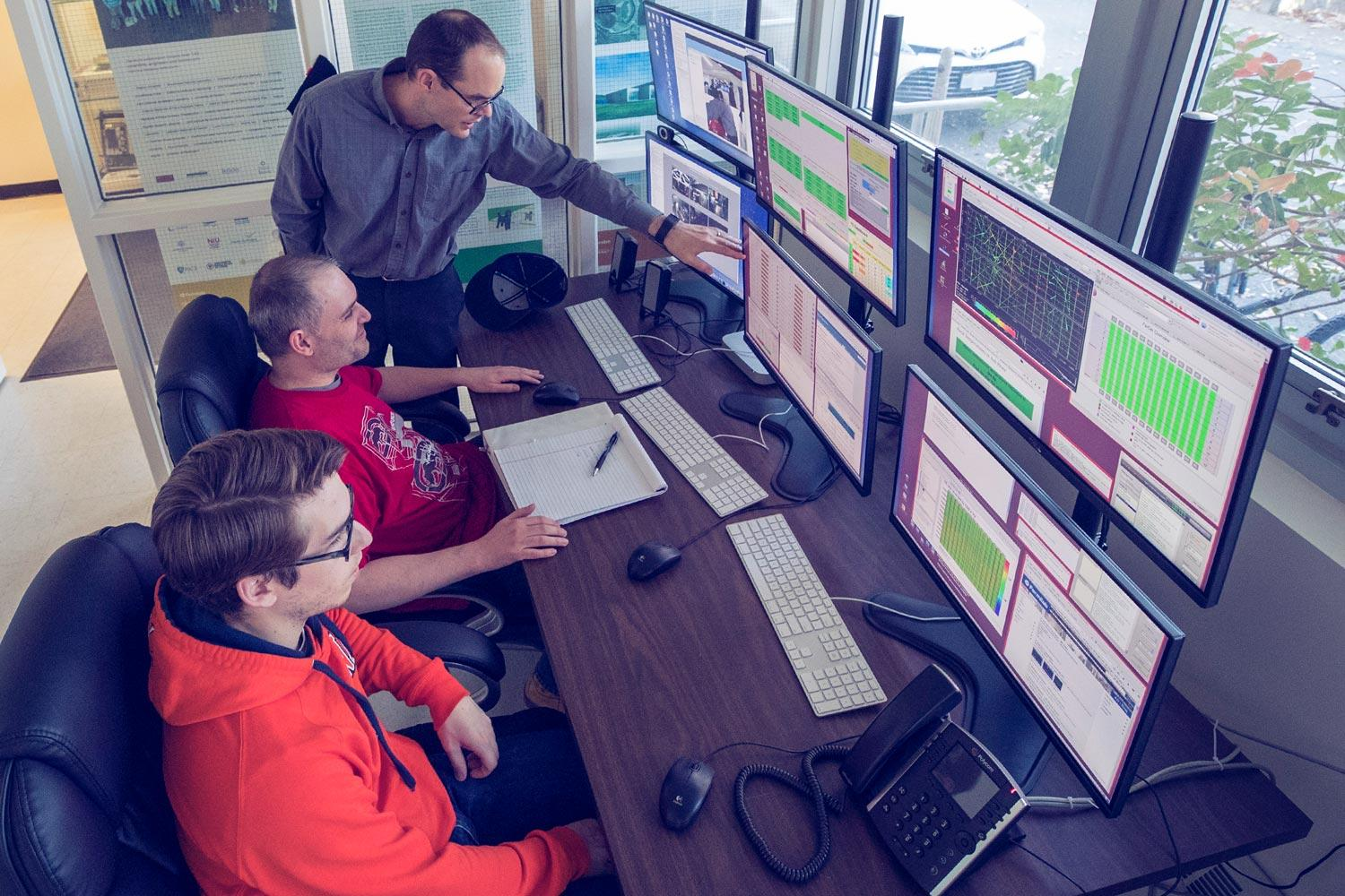 Physicists Craig Group (top) and Ralf Ehrlich and physics student Peter Farris at the NOvA monitor and control station installed at UVA by Ehrlich.