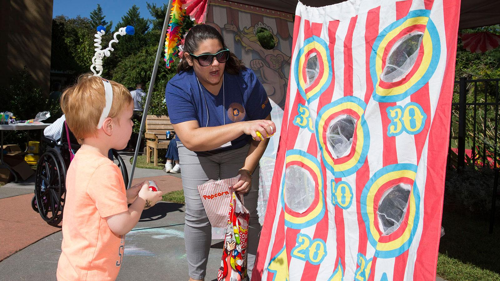 Volunteers from the Office for Diversity and Equity and the psychology department play games with preschoolers at a carnival at JABA.