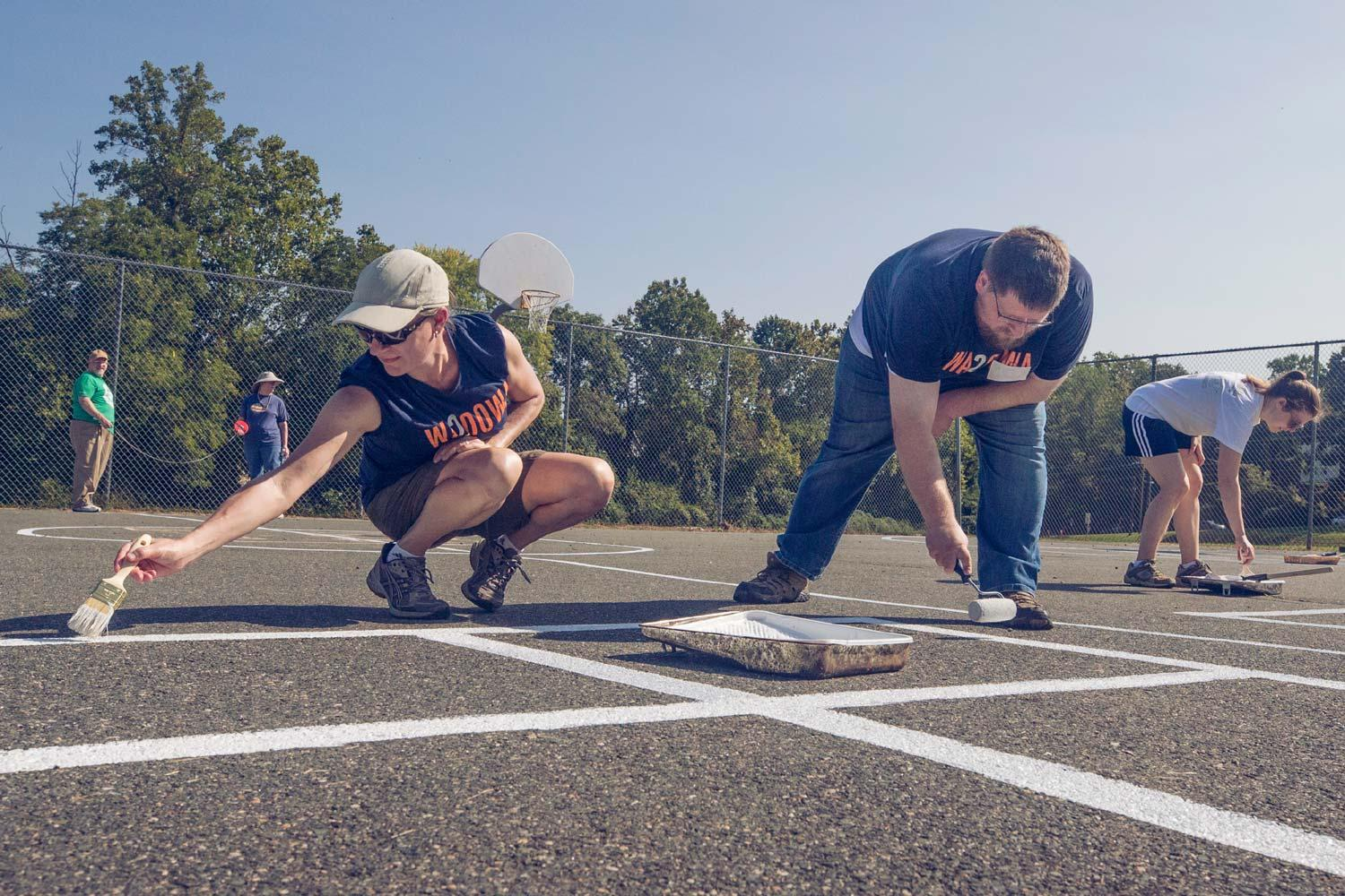 UVA employees Debbie Mincarelli and Tyler Miller paint lines on an outdoor basketball court at Burley Middle School in Charlottesville.