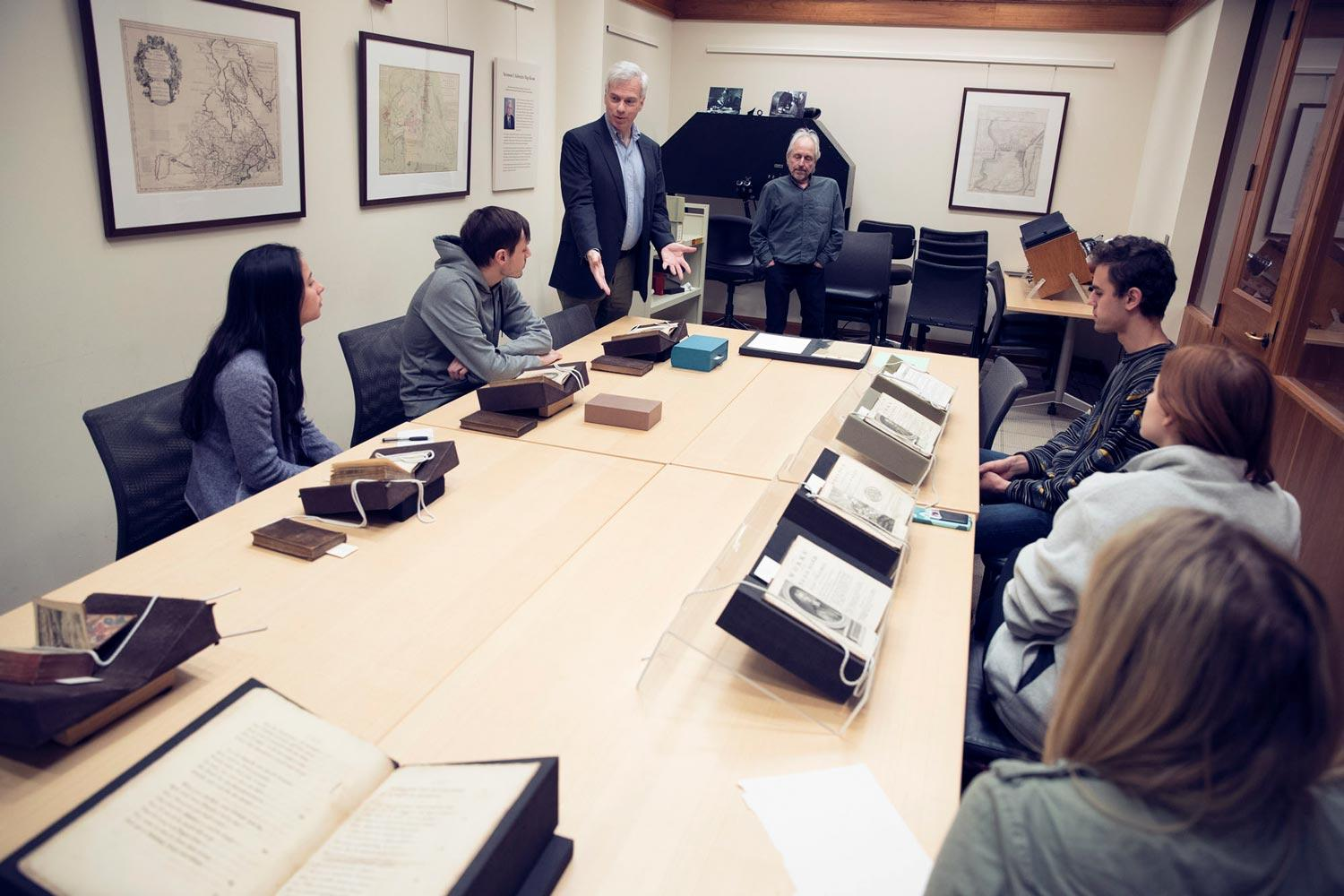 """Early editions of a classic like """"Gulliver's Travels"""" still excite John O'Brien, standing, and his students. George Riser (center, standing) of the University Library set up the books for viewing. (Photos by Dan Addison, University Communications"""