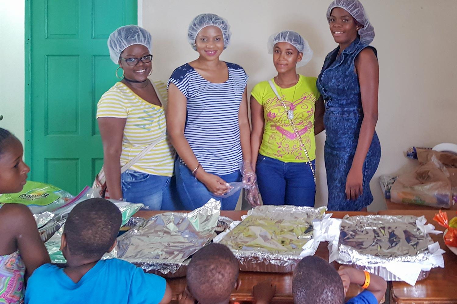Nursing graduate student Christina Ross, second from left, lead a relief effort to her home of Antigua, which was ravaged by Hurricane Irma. She and other volunteers also made and shared treats with local children.