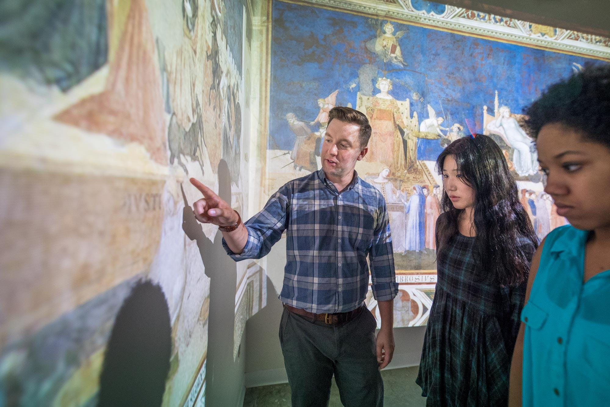 "Hupe and his students examine projections of Renaissance artist Ambrogio Lorenzetti's ""Allegory and Effects of Good and Bad Government."""