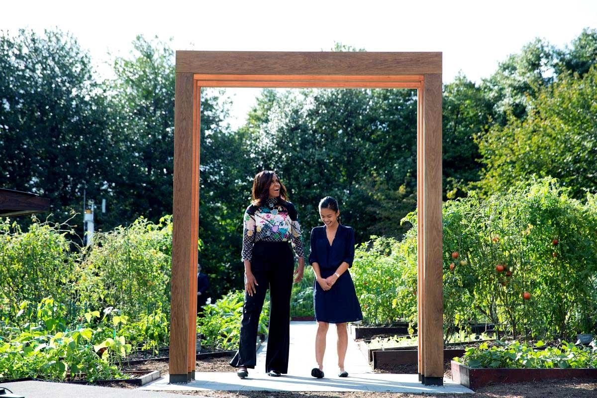 "First lady Michelle Obama stands with Tammy Nguyen, a student participating in the first lady's ""Let's Move!"" initiative, beneath a new arbor designed by UVA students for the White House Kitchen Garden."