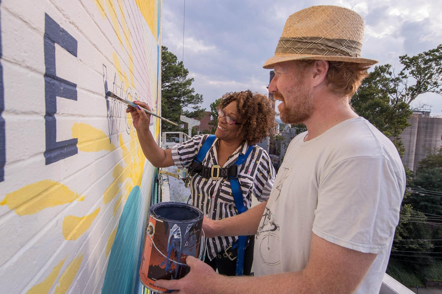 Muralist David Guinn and UVA English professor and renowned poet Rita Dove put the finishing touches on a new mural featuring Dove's poetry. (Photo by Sanjay Suchak, University Communications)