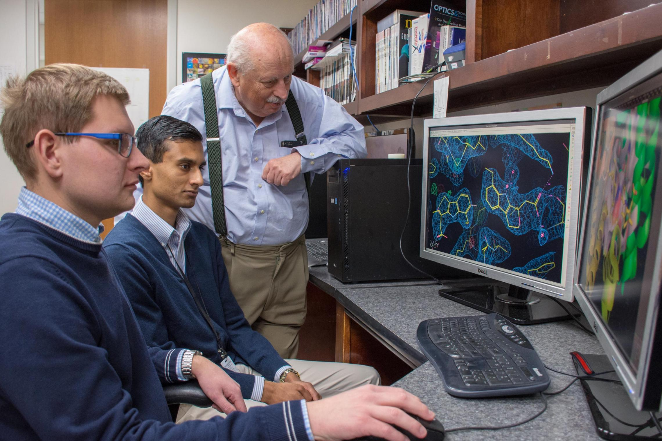 Graduate student Mateusz Czub, left, and undergraduate chemistry student Barat Venkataramany, center, analyze a testosterone binding site and discuss the possible medical implications of their finding with Wladek Minor.