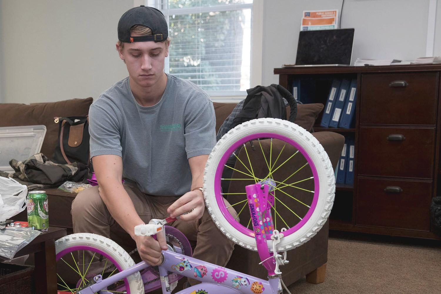 Aidan Kilrain, a third-year biology major and Holiday Sharing program director, assembles a bicycle for one of the Holiday Sharing gifts to a family in need.