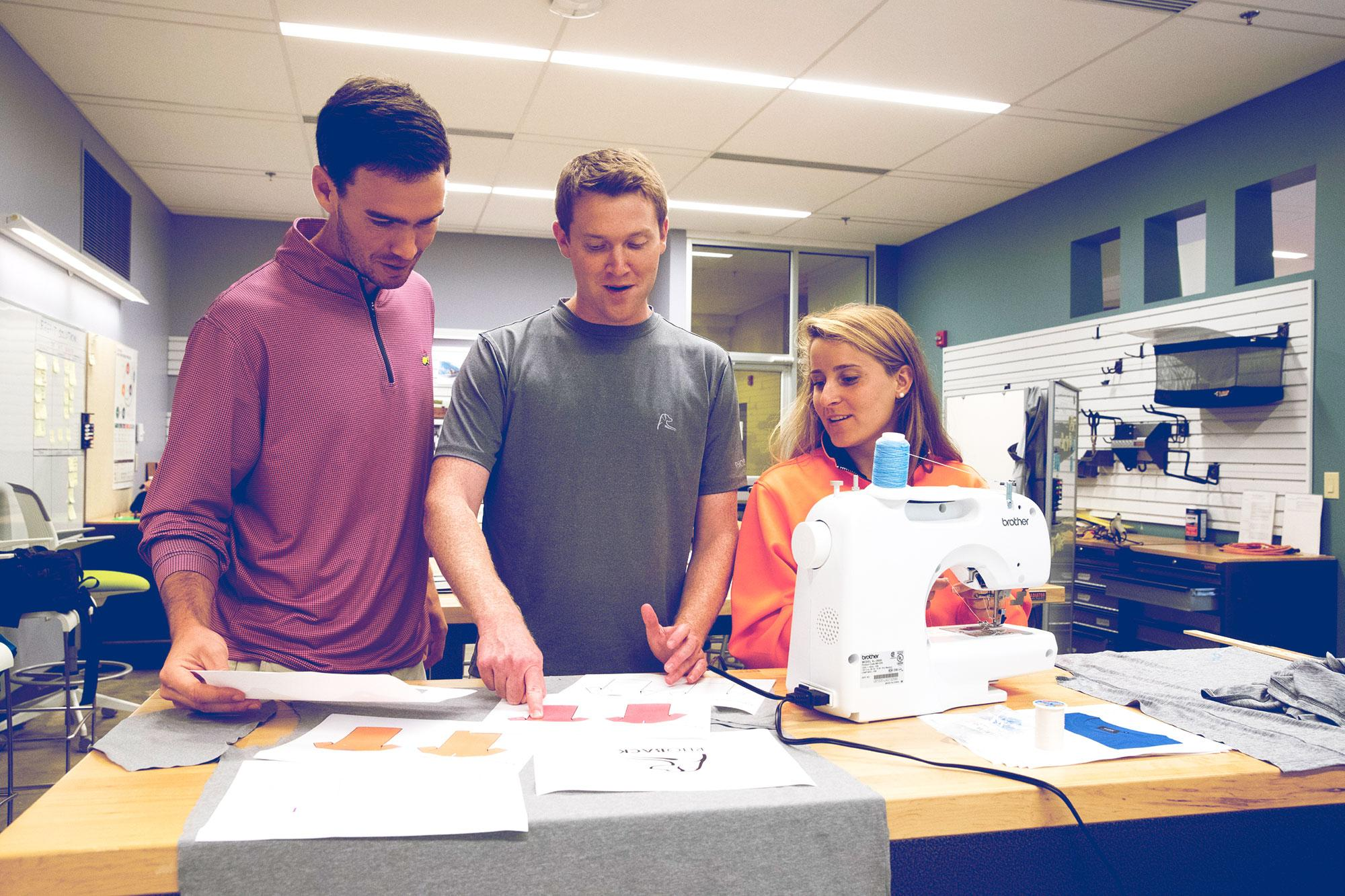 Matt Loftus, left, friend and business partner Kevin Hubbard and wife Kristina Loftus, shown here in UVA's iLab, had little idea that a pair of orange pants would spark their next business.