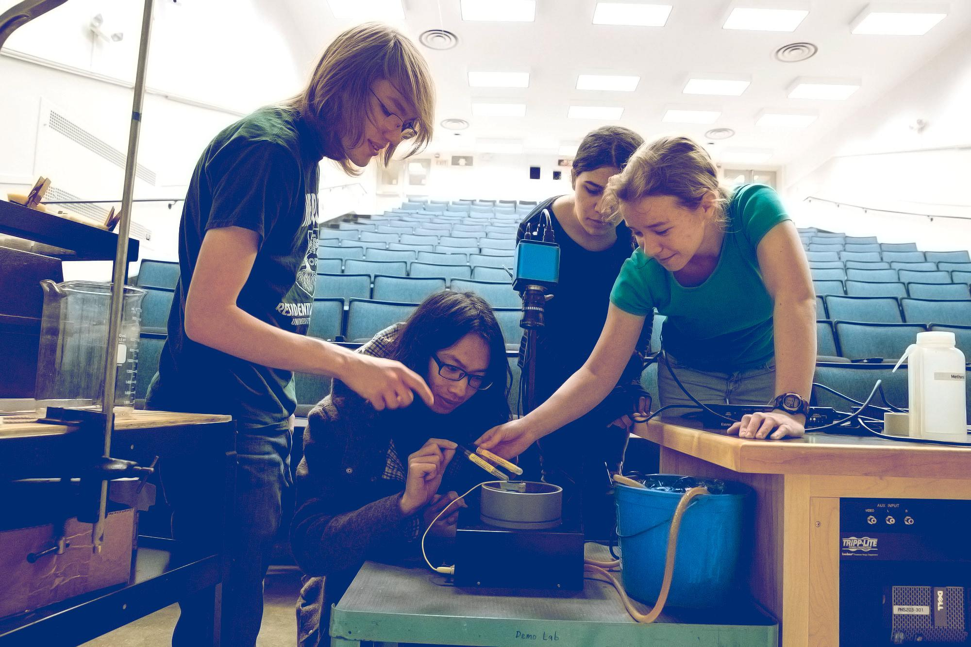 Undergraduate students Katya Gilbo, Yara Yousef, Chris Li, and Steven Stetzler prepare a demonstration for tonight's show that will allow observation of cosmic rays.