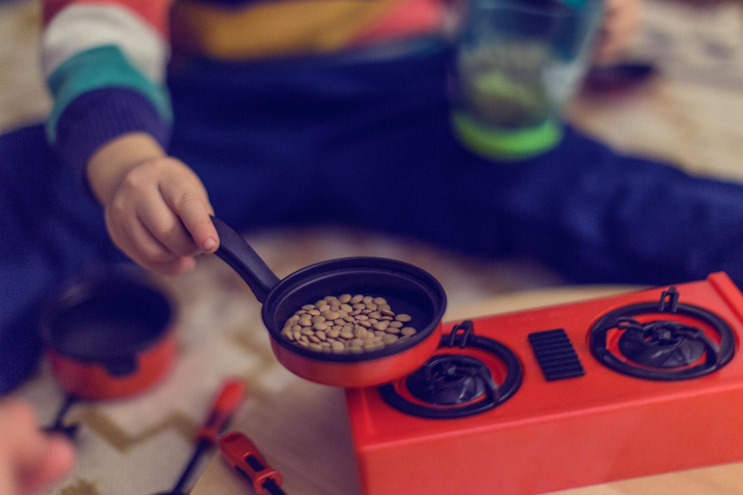 Small child's hand holding a toy pot filled with lentils