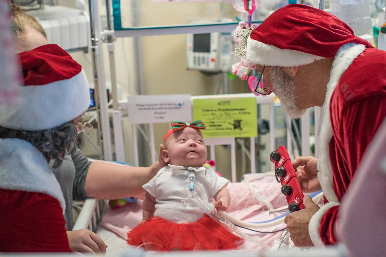 "Santa Claus, right, portrayed by neonatologist Dr. Robert Sinkin, and ""Mrs. Claus"" visit a patient in the NICU on Wednesday. (Photos by Sanjay Suchak, University Communications)"