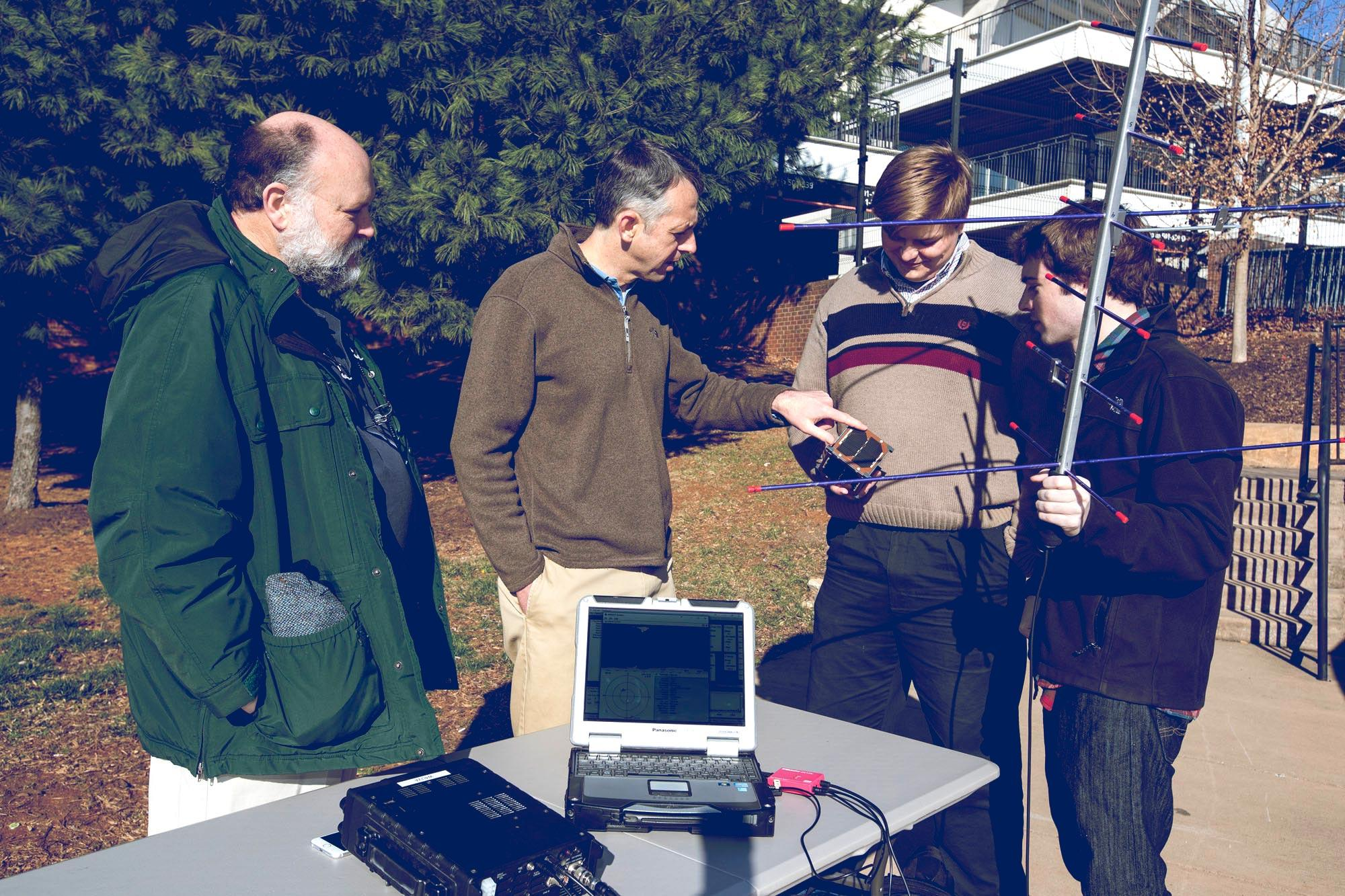 Amateur radio club trustee Michael McPherson, left, Professor Chris Goyne and engineering students Colin Mitchell and Tyler Gabriele, attempt to track a satellite using a UHF radio and hand-held antenna. (Photo: Dan Addison University Communications)
