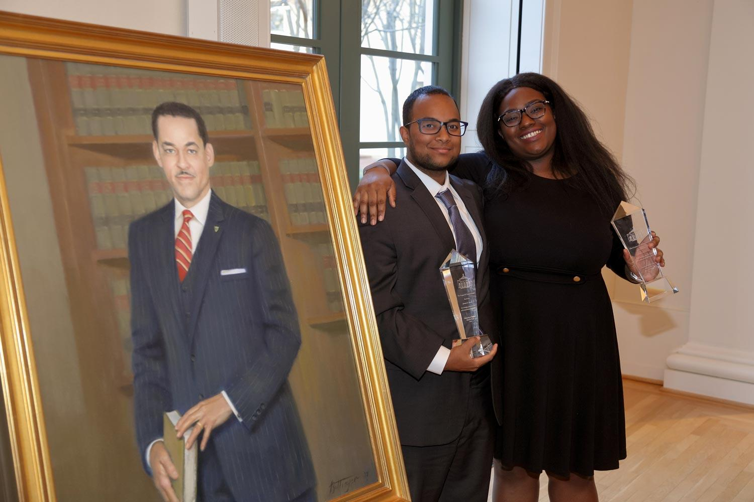 The inaugural Gregory H. Swanson Award was presented to second-year law students Jamaica Akande and Toccara Nelson. The award winners are pictured here with a portrait of Swanson, the first African-American admitted to UVA. (Photos by Tom Cogill)