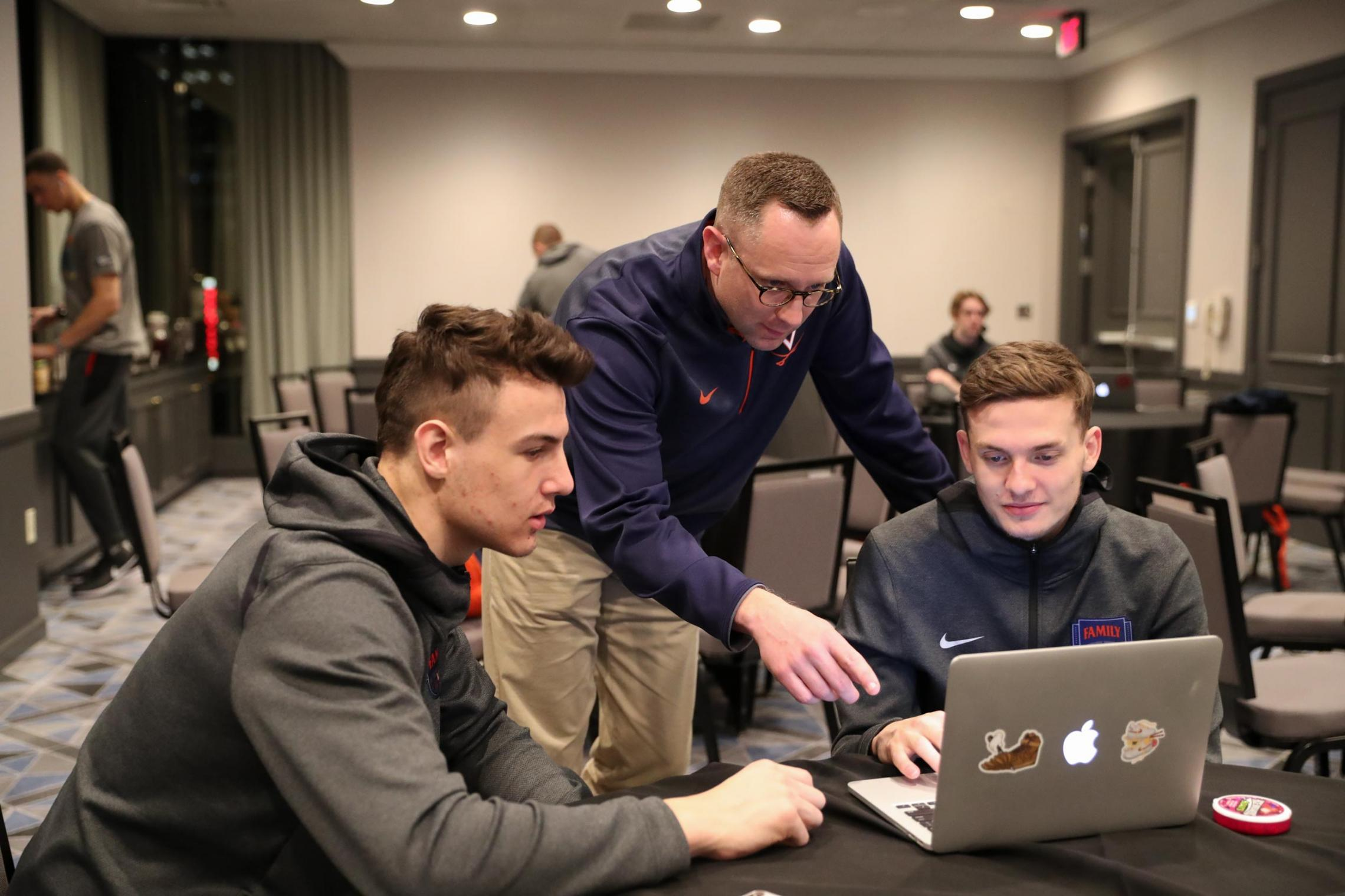 T.J. Grams, center, works with Francisco Caffaro, left, and Kyle Guy at a study hall Wednesday in Minneapolis. Grams helps players connect with professors and the academic resources they need to succeed. (Photo by Matt Riley, UVA Athletics)