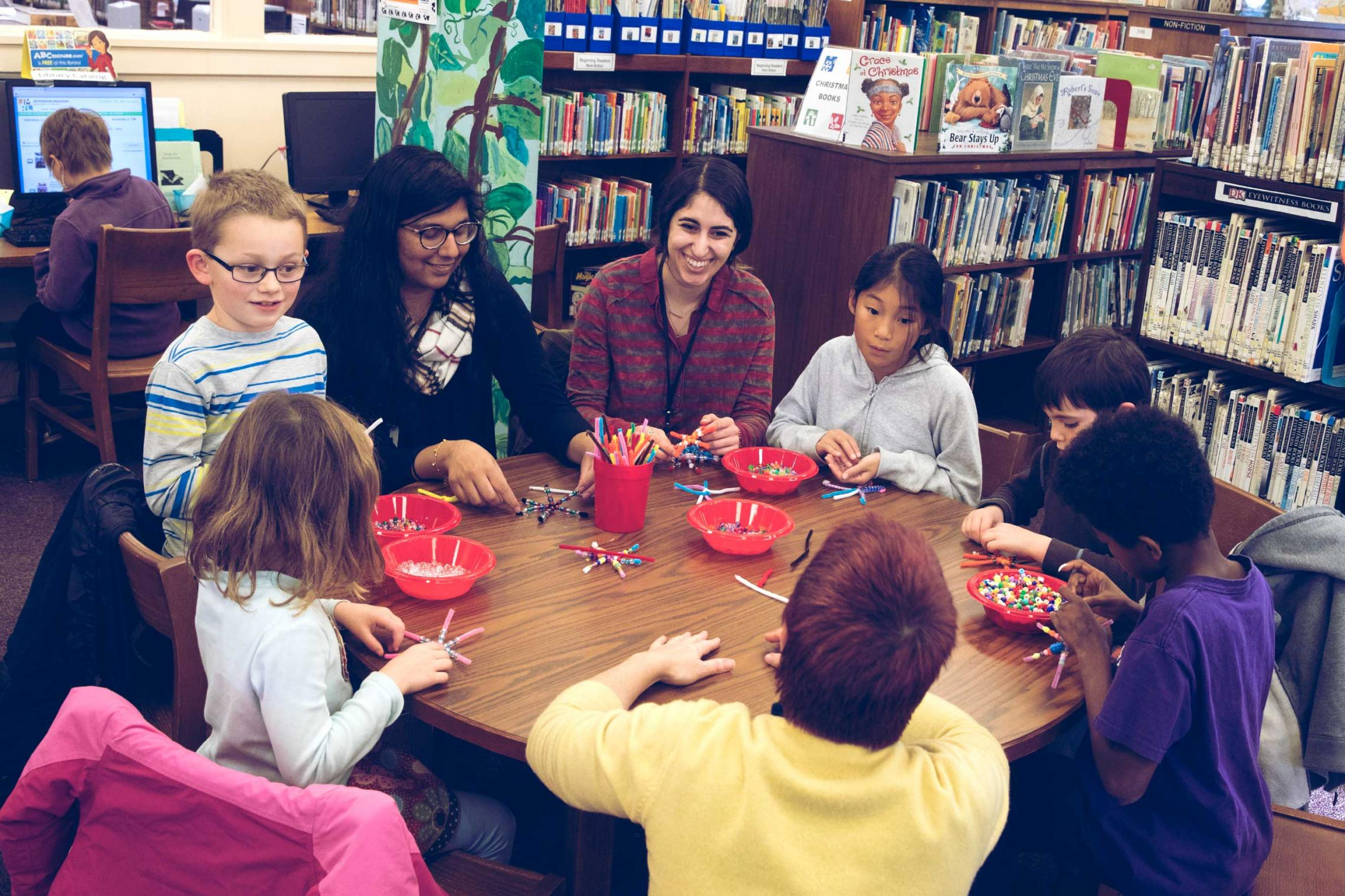 Lajja Patel, a third-year biology major, and Darya Tahan, a second-year student, work with children on creative projects, as well as help maintain the toy library.