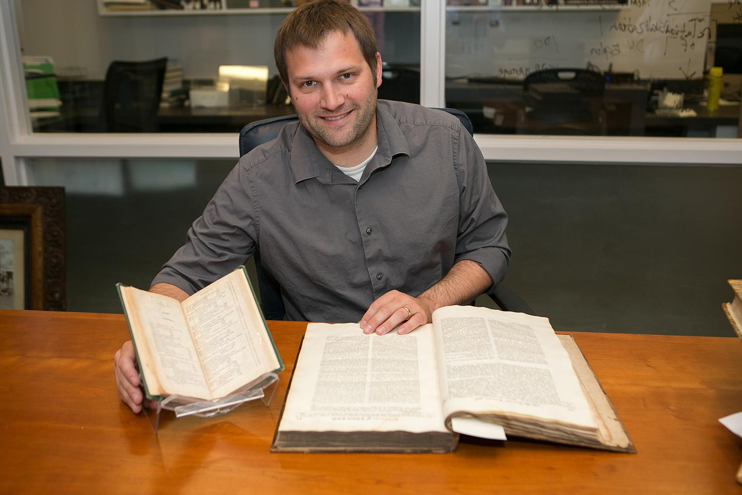 Digital Collections Librarian Loren Moulds shows a book from the catalogue, and the catalogue itself.
