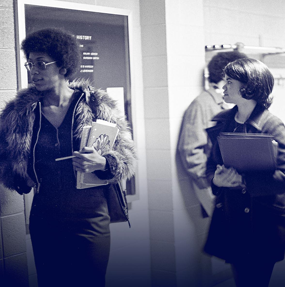 Two women waiting outside a classroom with books