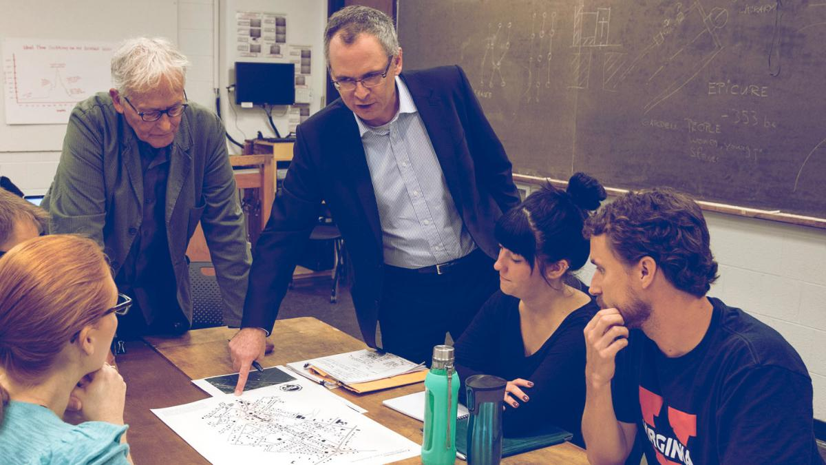 Johnston, standing at right, and French architect Philippe Revault, left, talk with students about their ideas for community revitalization projects in Gordonsville. (Photo by Dan Addison, University Communications)