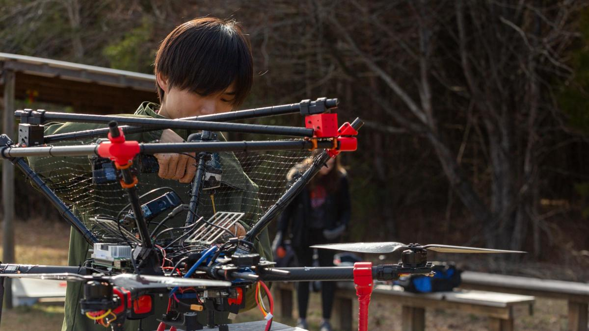 A student from Team VICTOR works on an aerial drone that can detect moving objects in the air at UVA's Milton Airfield.