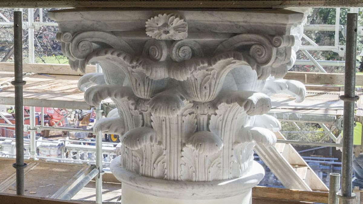 Workers remove plastic from the capitals