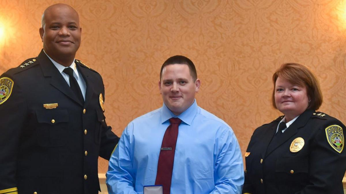Officer Dean Dotts, center, earned the Lifesaving Medal for administering CPR to an unresponsive person in a parking garage. He is flanked by Chief Tommye Sutton, left, and Deputy Chief Melissa Fielding. (Submitted photo)