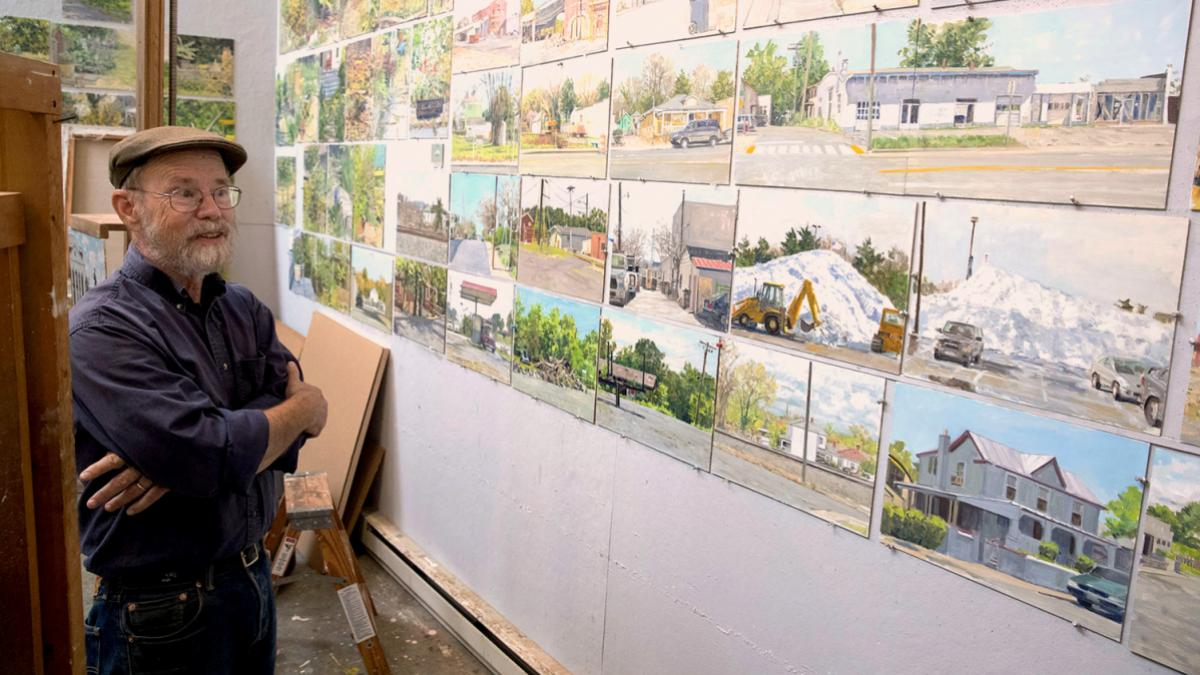 Professor Emeritus Richard Crozier at work in his studio, surrounded by scenes of Charlottesville and UVA.