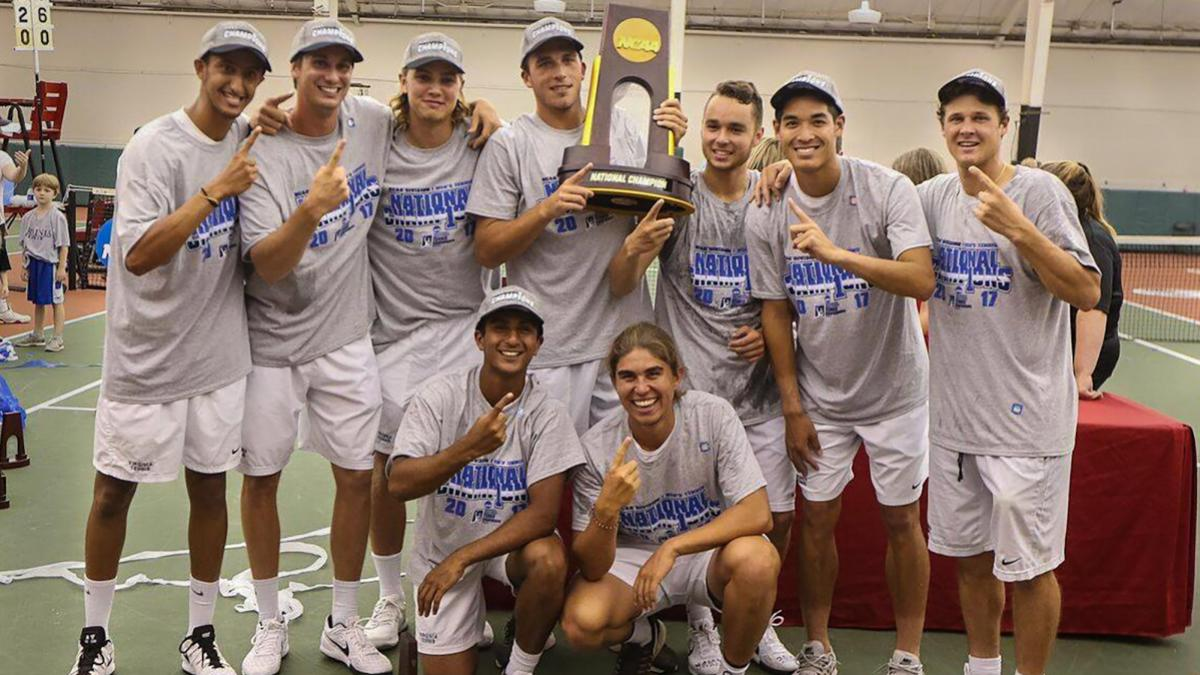 The Cavaliers celebrate Tuesday after J.C. Aragone's clinching victory at No. 5 singles inside the Dan Magill Tennis Complex's indoor facility at the University of Georgia. (Photo by Matt Riley, UVA Athletics)