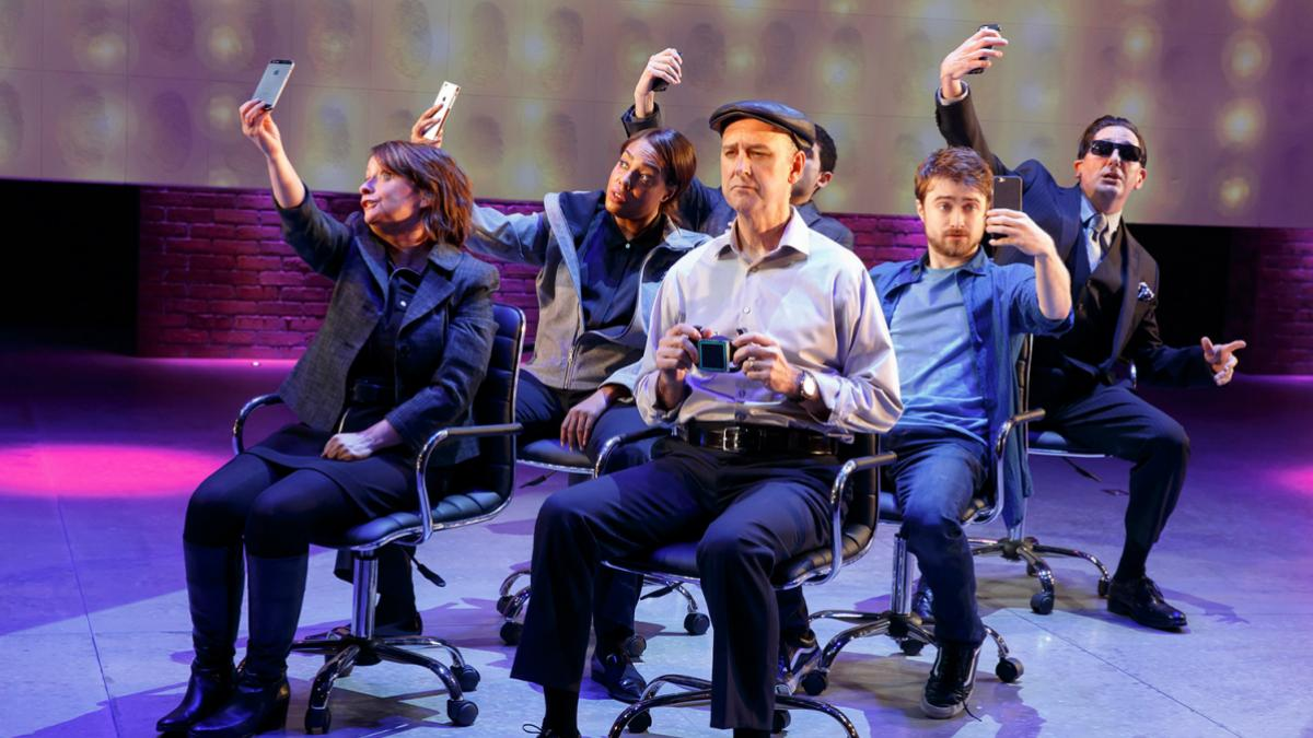 """Privacy"" cast members take selfies on stage. From left to right: Rachel Dratch, De'Adre Aziza, Michael Countrymen, Daniel Radcliffe and Reg Rogers. Raffi Barsoumian sits in the back left. (Photo by Joan Marcus)"