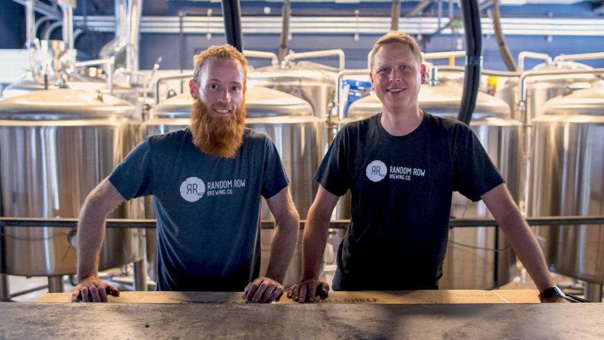 Health System employee Kevin McElroy, left, and Darden grad Bradley Kipp stand behind the bar at Random Row Brewing Co. (Photo by Sanjay Suchak/Univ