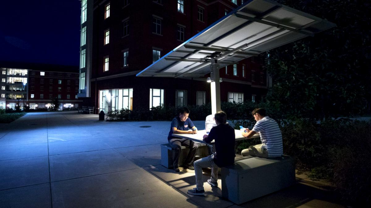 A student initiative resulted in the installation of a solar table outside Lile-Mapuin House, where students can recharge batteries while collaborating on projects. (Photo by Sanjay Suchak, University Communications)