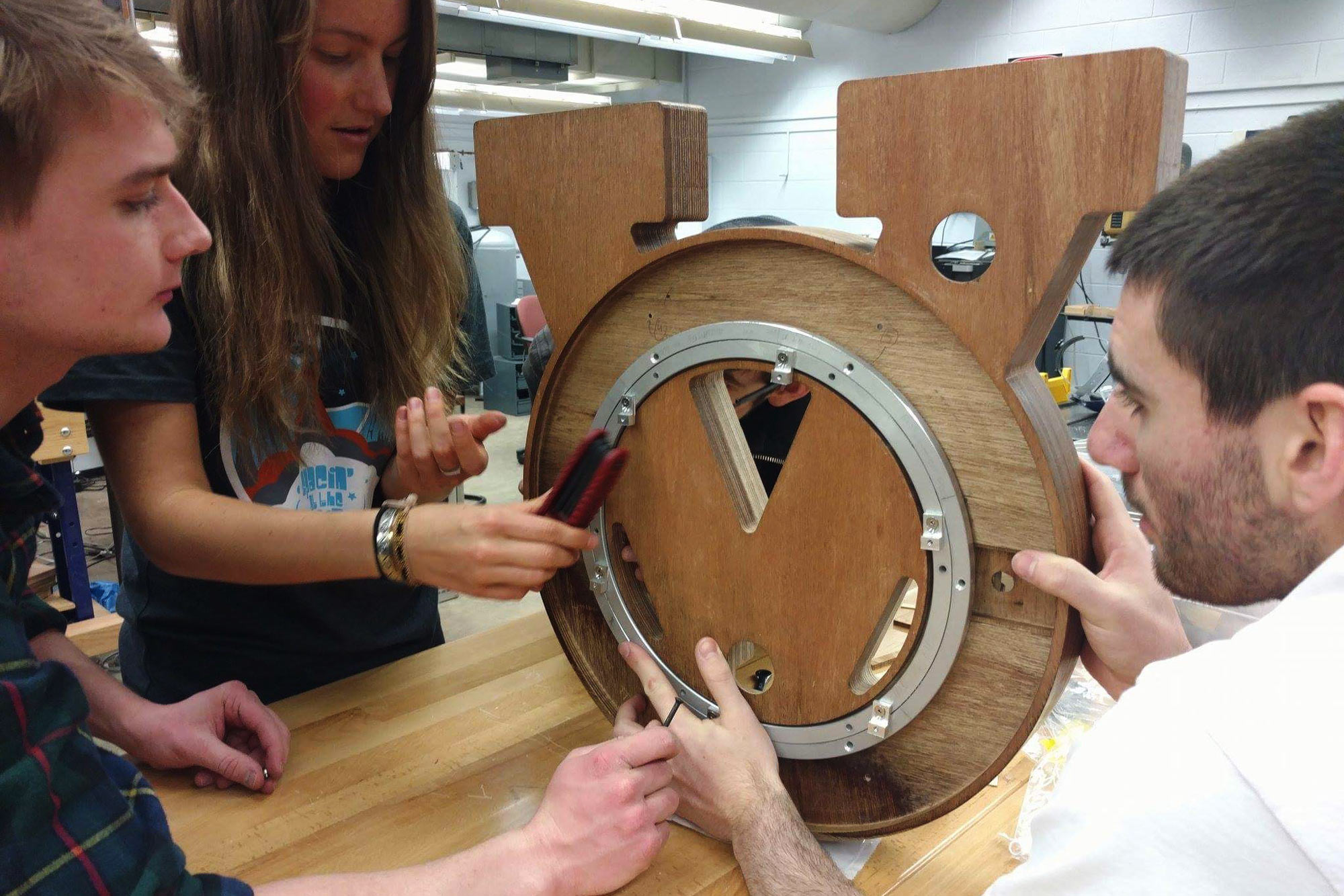 Three students building a clock