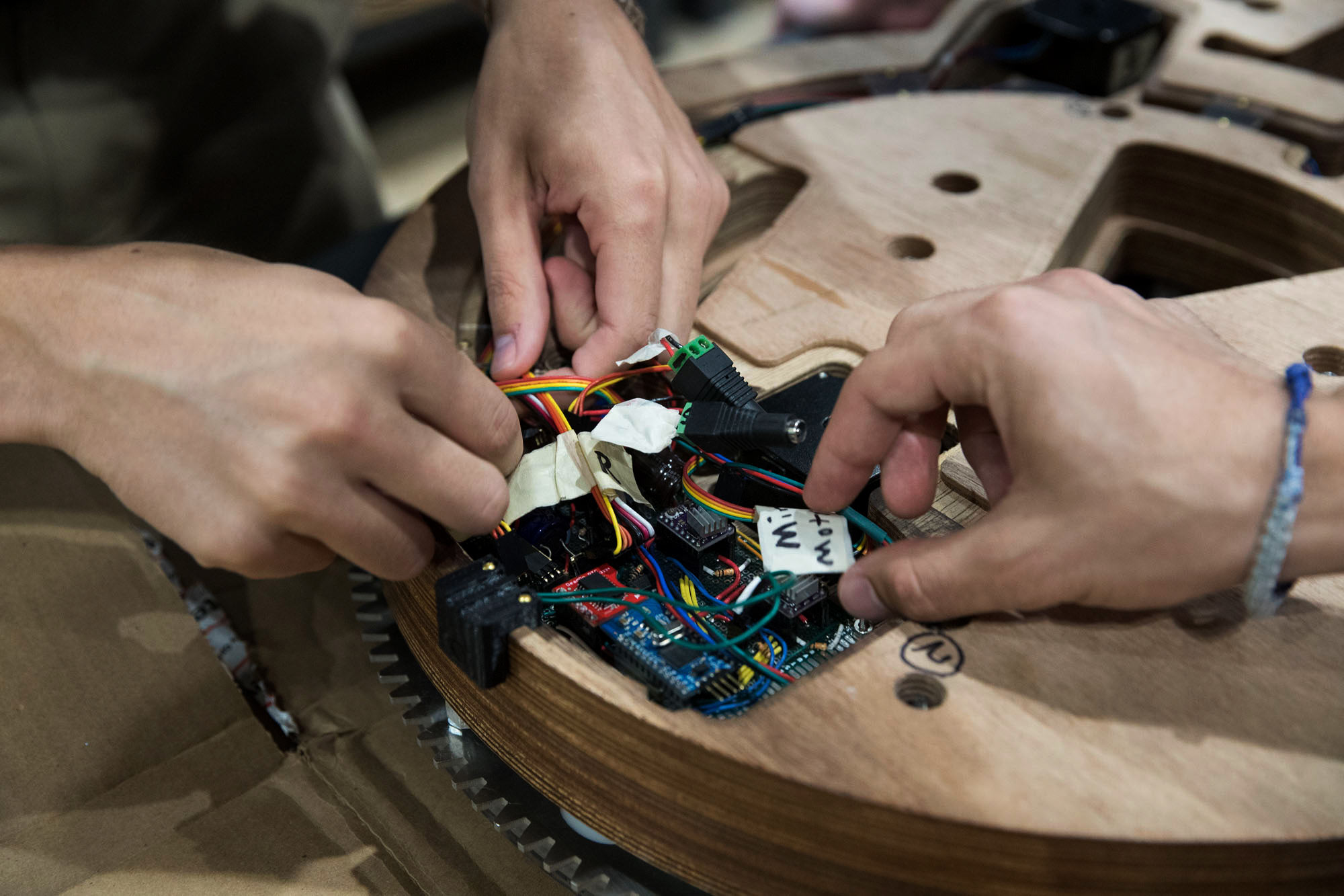 Hands placing electronics in the back of an unfinished wooden clock