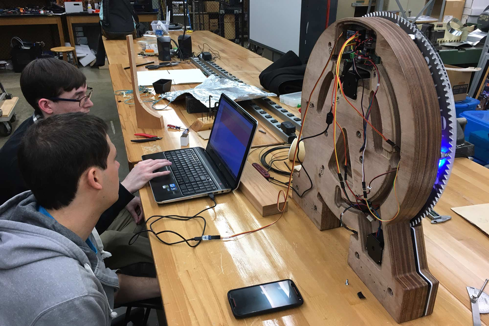 Two students using a computer to program a clock