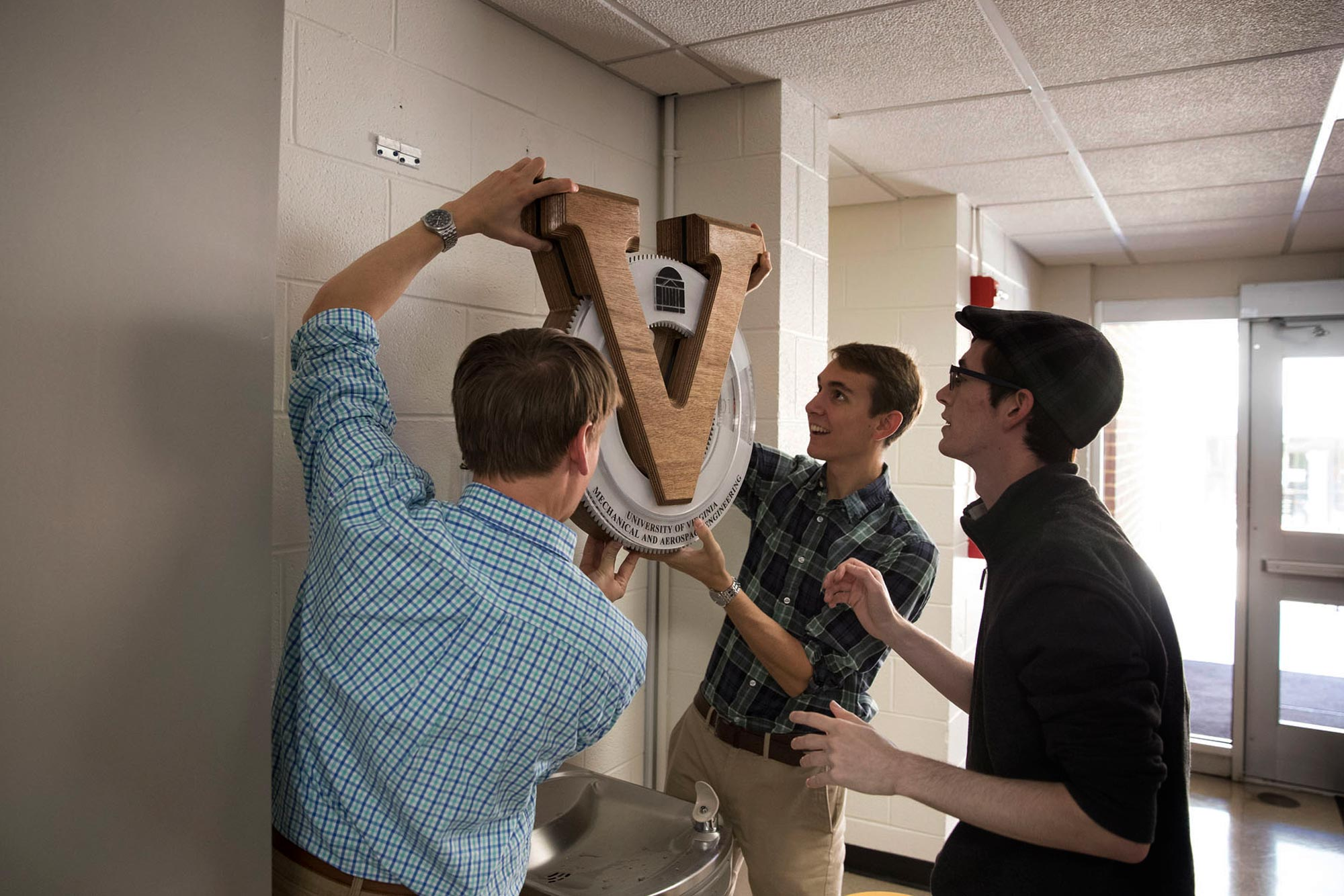 Three students hanging a clock in a hallway over a waterfountain
