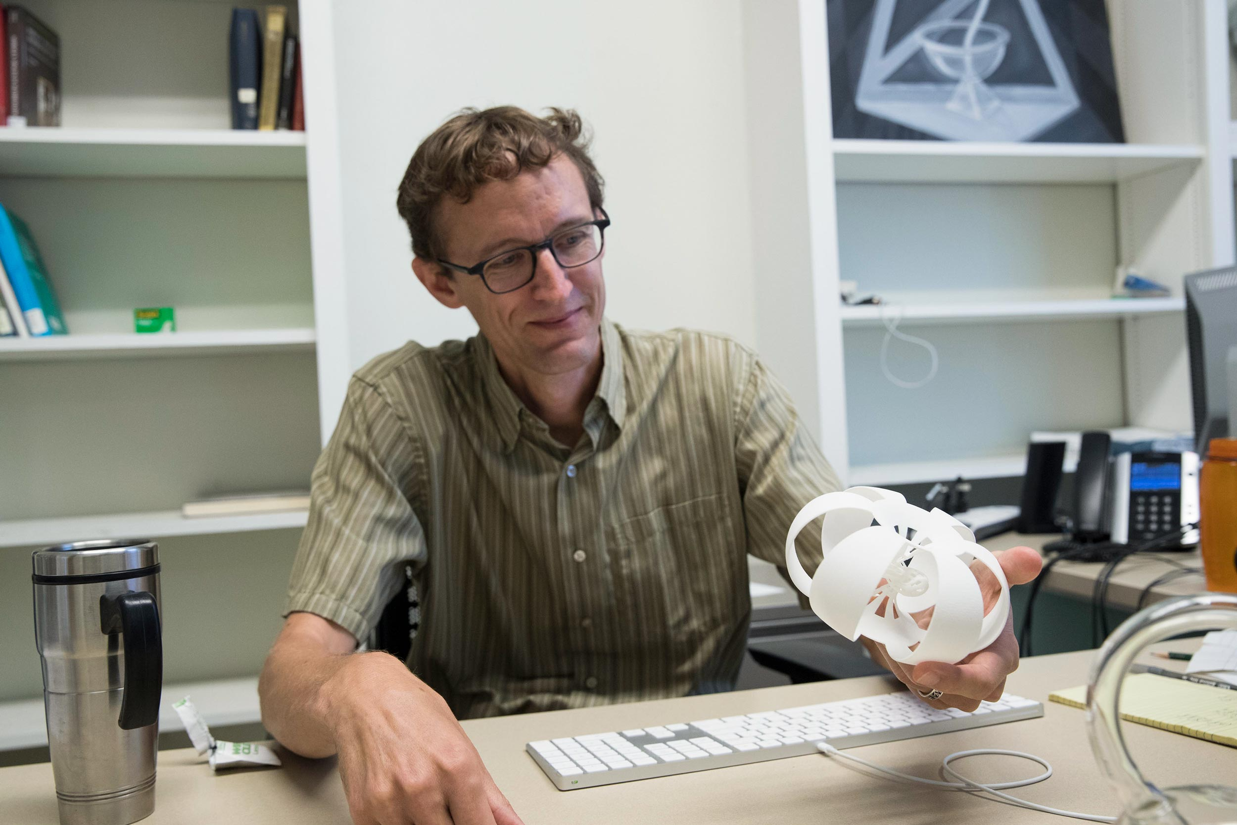 Mathematics professor Thomas Mark, holding a 3-D-printed representation of a multi-dimensional shape, co-wrote the proposal that won the NSF grant.
