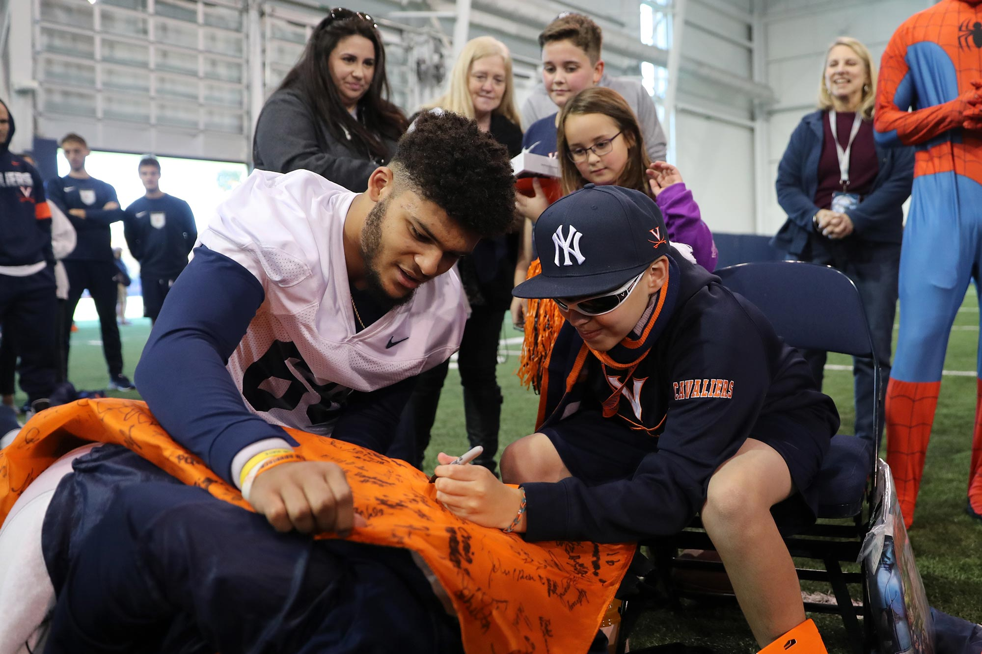 UVA first-year football player Chayce Chalmers helps a recent Thursday's Hero sign a keepsake flag.